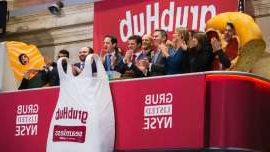 a man holding a sign: GrubHub on the New York Stock Exchange.