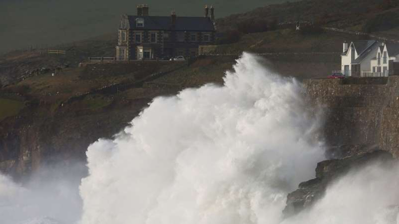 a man riding a wave on top of a snow covered mountain: Storm Ciara lashes Porthleven in Cornwall last weekend