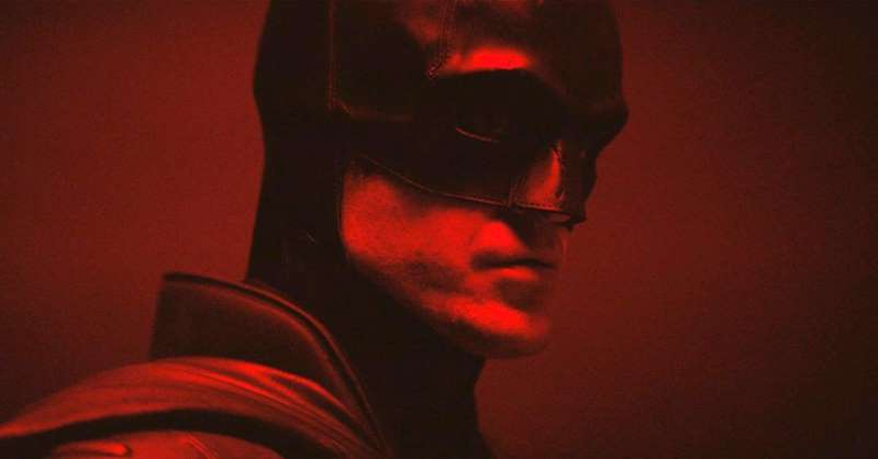 a man wearing a red light in a dark room: Warner Bros. Studios Robert Pattinson as The Batman