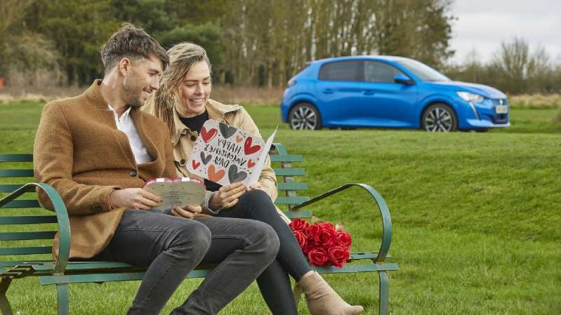 a woman sitting on a bench in a park: Peugeot e-208 goes far enough for long-distance relationships