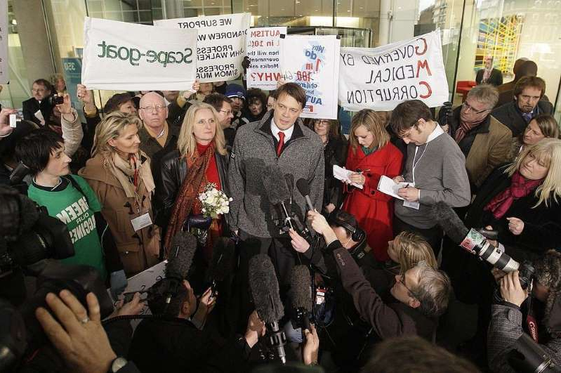 Andrew Wakefield et al. standing in front of a crowd posing for the camera
