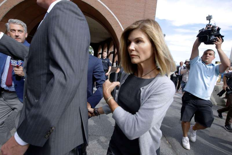 FILE - In this Aug. 27, 2019, file photo, actress Lori Loughlin departs federal court in Boston, after a hearing in a nationwide college admissions bribery scandal. A new prosecution filing in the college admissions cheating case targets defense claims by Loughlin and her fashion designer husband Mossimo Giannulli. The Los Angeles Times reports the filing Tuesday, Jan.14, 2020, includes hundreds of pages of emails, transcripts of recorded calls and financial and academic records. (AP Photo/Steven Senne, File)