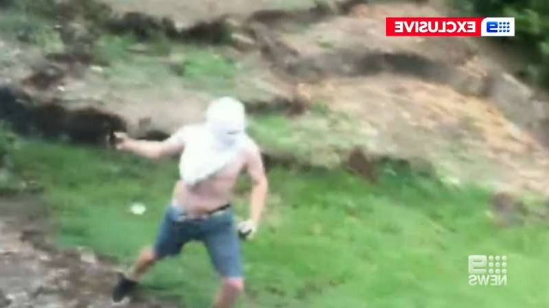 Footage shows a young male with a t-shirt over his head and a spay can in hand.