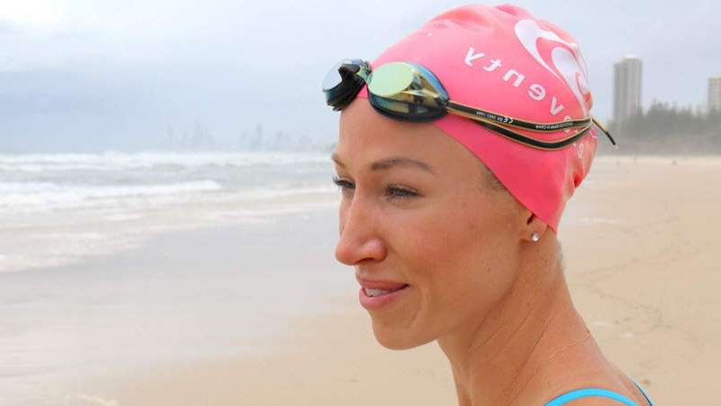 a woman wearing a hat and sunglasses posing for the camera: Open water swimmer Jessica Evans has been training on the Gold Coast. (ABC News: Michael Rennie)