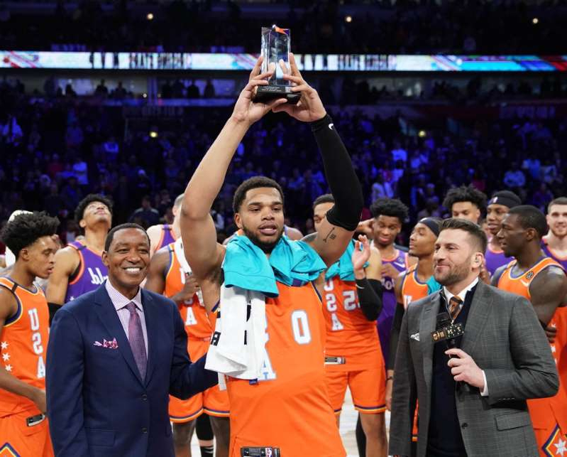Jared Greenberg, Isiah Thomas standing on a stage in front of a crowd: USA forward Miles Bridges of the Charlotte Hornets hoists the MVP trophy during the NBA Rising Stars basketball game at United Center on February 14, 2020.