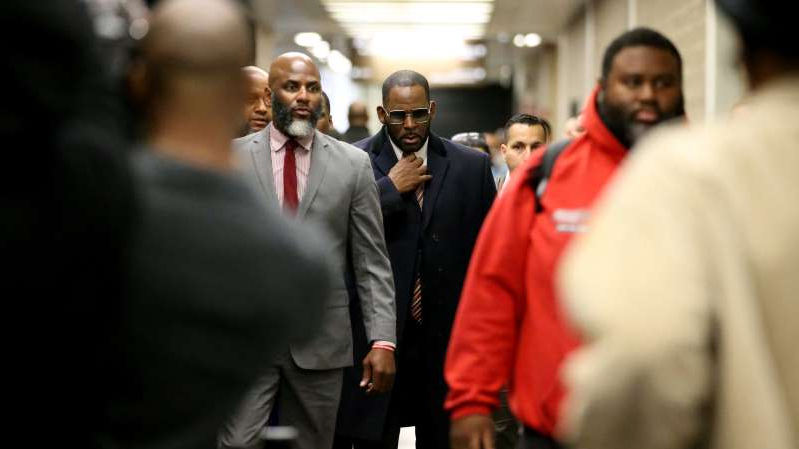 R. Kelly wearing a suit and tie talking on a cell phone: R. Kelly, center, appears at the Daley Center in Chicago on May 8, 2019, for a hearing in his child support case.