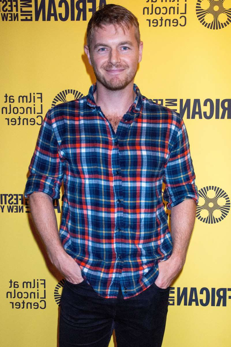 Rick Cosnett holding a sign posing for the camera: Rick Cosnett attends the 26th New York African Film Festival in New York City on May 30, 2019.