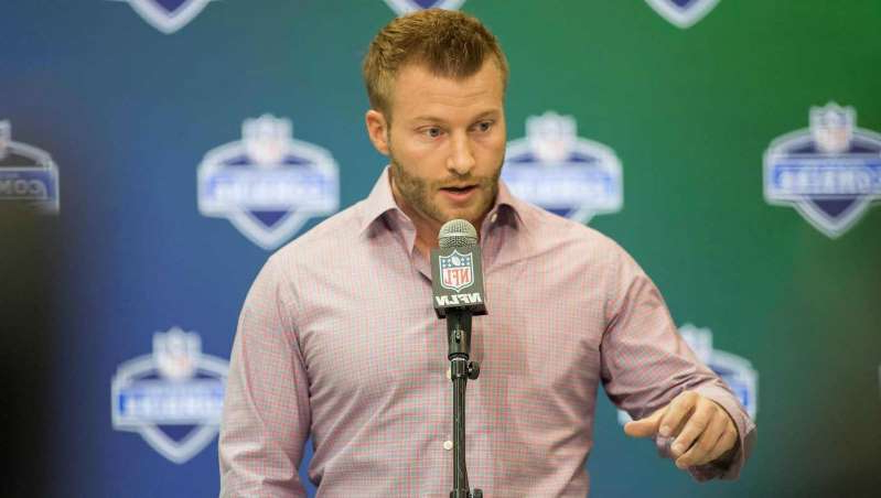 Sean McVay standing in front of a microphone: Mar 2, 2017; Indianapolis, IN, USA; Los Angeles Rams head coach Sean McVay speaks to the media during the 2017 combine at Indiana Convention Center.