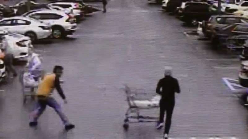 a group of people walking down the street: Raw video: Georgia shopper stops thief by pushing grocery cart in thief's path.