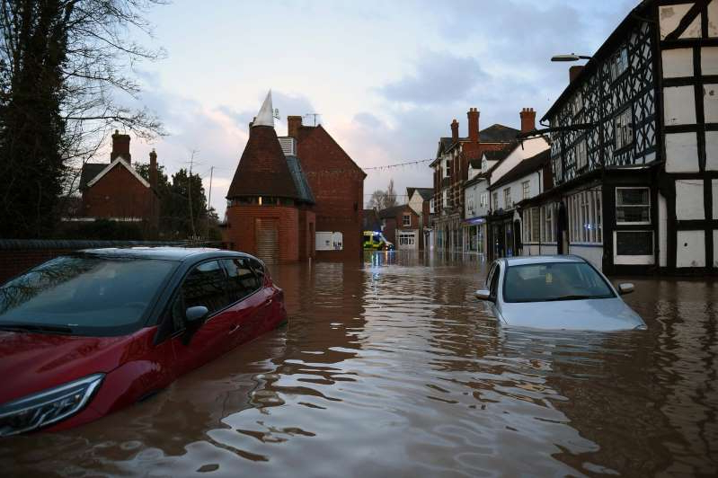 a car parked in front of a house covered in snow: Floodwater surrounds abandoned cars in Tenbury Wells, in western England, after the River Teme burst its banks on Sunday. (Oli Scarff/AFP/Getty Images)