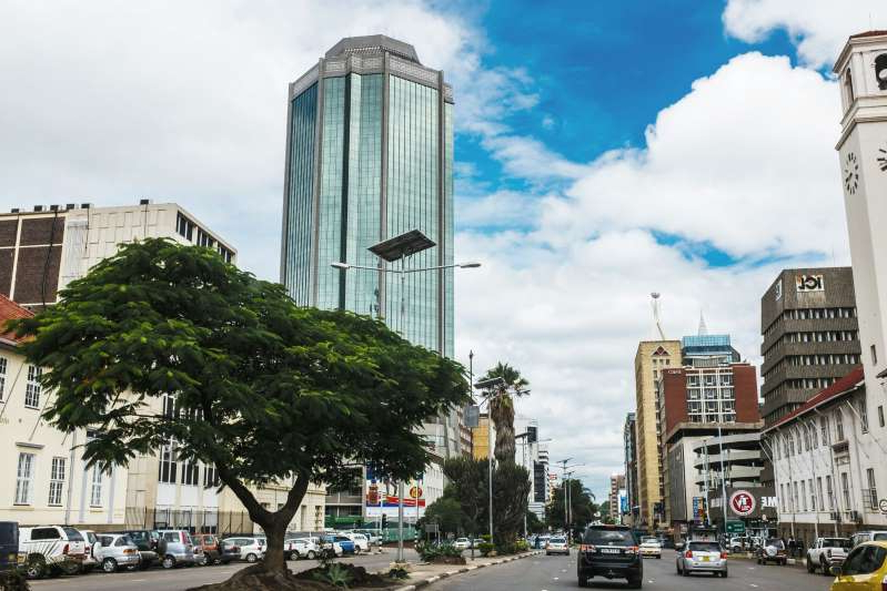 a close up of a busy city street: The Reserve Bank of Zimbabwe tower in Harare.