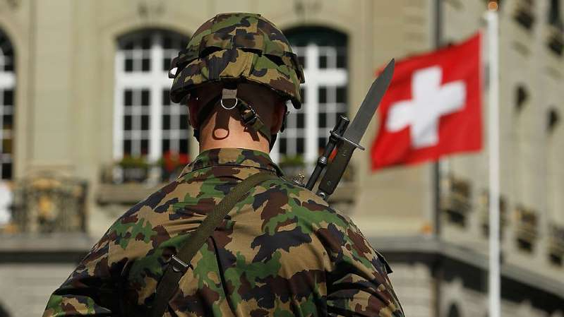 a man in a uniform standing in front of a building: Has the Crypto AG scandal shattered Swiss neutrality?