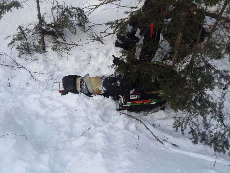 a man riding a snowboard down a snow covered slope: The man was seriously injured in the crash.