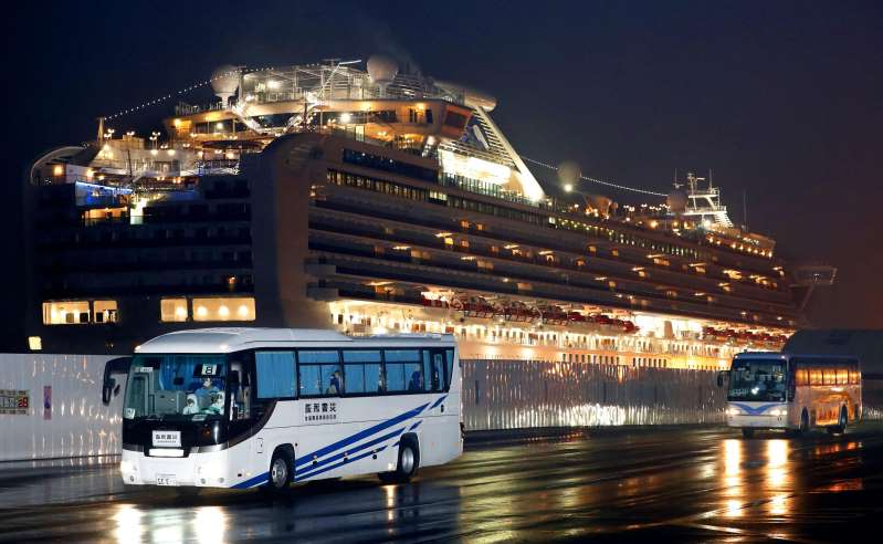Buses carrying U.S. passengers who were aboard the quarantined cruise ship the Diamond Princess, seen in background, leaves Yokohama port, near Tokyo, early Monday, Feb. 17, 2020. The cruise ship was carrying nearly 3,500 passengers and crew members under quarantine. (Jun Hirata/Kyodo News via AP)