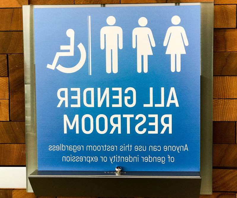 a close up of a sign: All gender restroom
