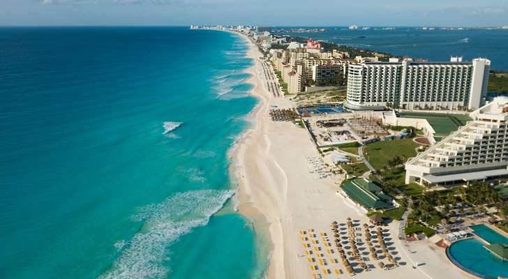 a couple of lawn chairs sitting on top of a beach: Aerial view of Cancun's Zona Hotelera