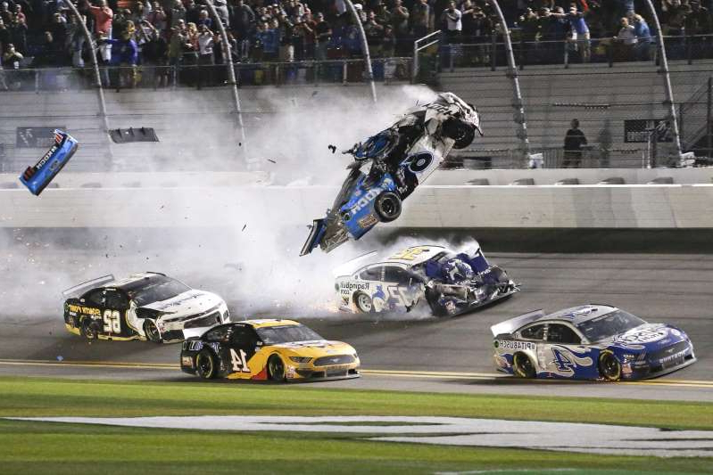 a group of people riding skis on top of a car: Ryan Newman (6) goes airborne as he collided with Corey LaJoie (32) on the final lap of the NASCAR Daytona 500 auto race at Daytona International Speedway, Monday, Feb. 17, 2020, in Daytona Beach, Fla. Sunday's race was postponed because of rain. (AP Photo/Terry Renna)