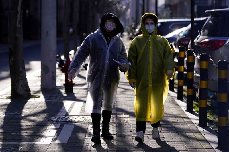 a man walking down the street: Women wear face masks and plastic raincoats as a protection from coronavirus in Shanghai