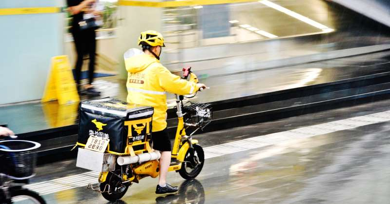 a person riding on the back of a motorcycle: A Meituan food delivery worker on motorcycle in the rain in Futian Central Business District, Shenzhen, China.