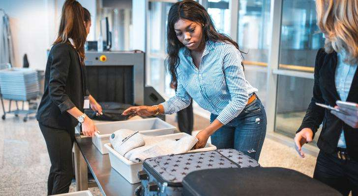 a woman sitting on a table: black woman, tsa, security, airport
