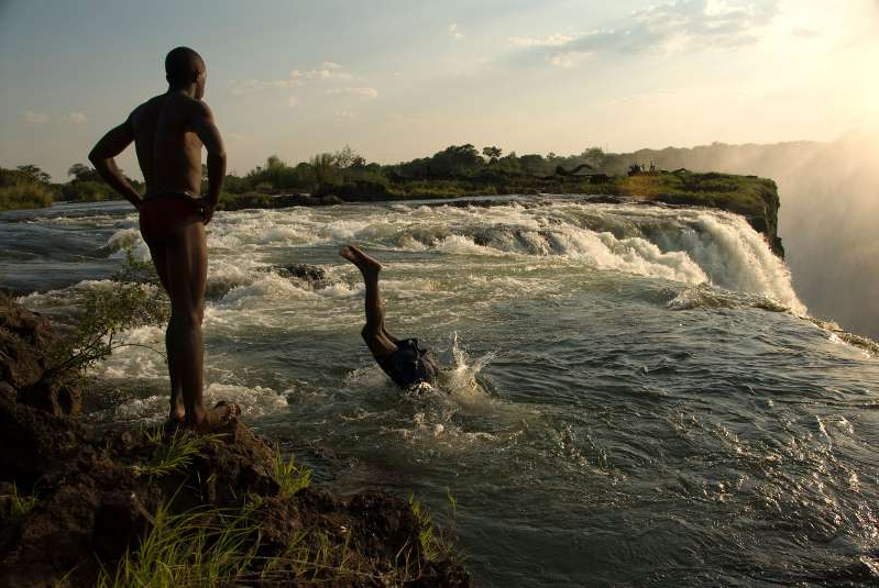 a man standing next to a body of water: Men dive into a swimming hole at the top of Victoria Falls.