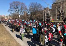 a group of people walking down the street in front of a crowd: Striking education workers say they want to send a message to the Ontario government that they are united and willing to continue job actions.
