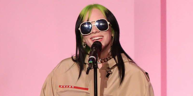 a person wearing a hat and sunglasses: Billie Eilish's James Bond theme No Time To Die has set a new record for the franchise after hitting the number one spot in the UK chart.