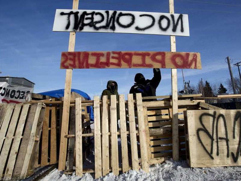 a sign over a wooden fence: Protesters block a CN rail line in Edmonton in solidarity with Wet'suwet'en hereditary chiefs, on Feb. 19, 2020.