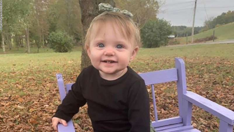 a little boy sitting on a bench posing for the camera: 15-month-old Evelyn Mae Boswell is still missing