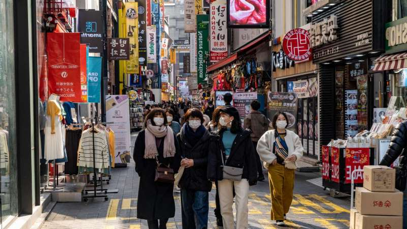 a group of people walking on a city street: South Koreans are still out and about in Seoul — though most people are wearing face masks as a precaution. (ABC News: Brant Cumming)