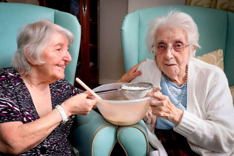 a man and a woman sitting on a plate: 104-year-old Rhiannon Grey Davies (left) who used to be a school domestic science teacher in Wrexham and her former pupil Joyce Jones