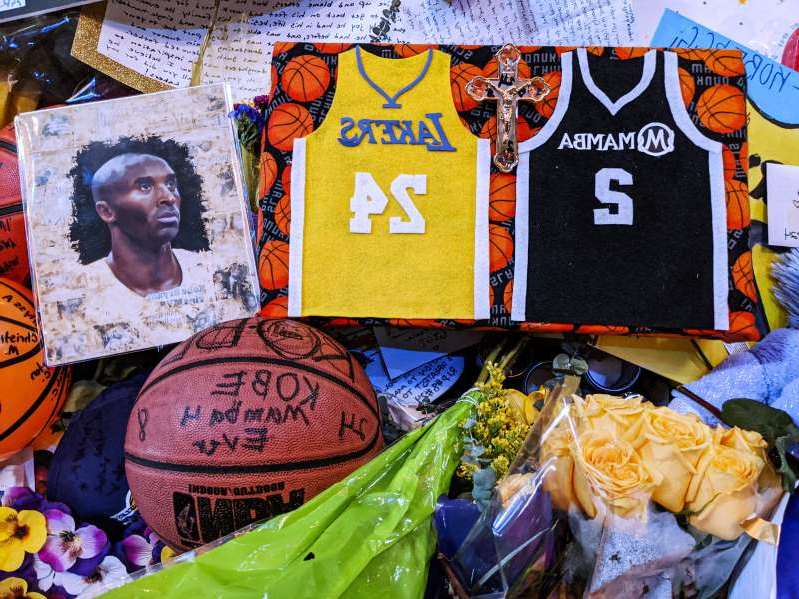 Memorabilia for NBA star Kobe Bryant are placed at a memorial for Bryant while fans gather to pay their respect near Staples Center.