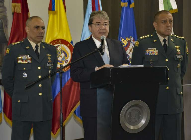 a group of people standing in front of a military uniform: Defence Minister Carlos Holmes Trujillo speaking during a press conference in Bogota on January 13, 2019