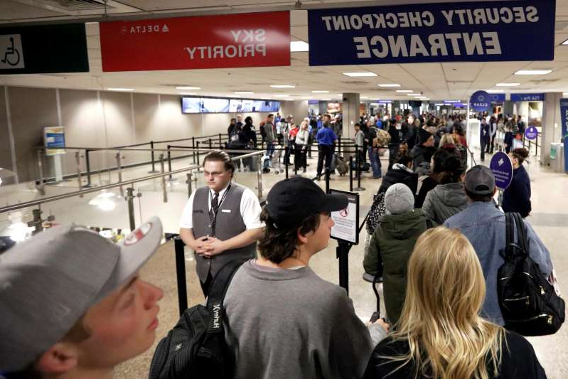 a group of people standing in front of a crowd: FILE - In this Wednesday, Nov. 27, 2019, file photo, travelers walk through a security checkpoint in Terminal 2 at Salt Lake City International Airport, in Salt Lake City. Federal officials are considering requiring that all travelers, including American citizens, be photographed as they enter or leave the country as part of an identification system using facial-recognition technology.