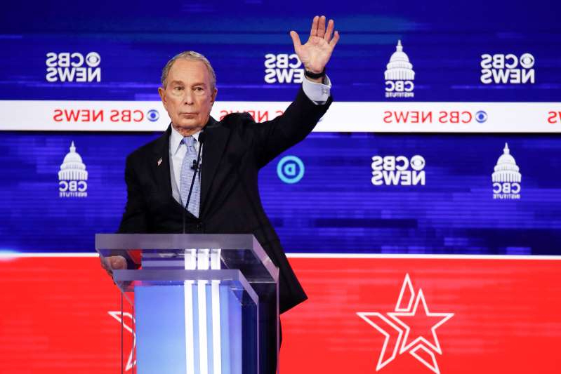 Michael Bloomberg standing in front of a television screen: Mike Bloomberg raises his hand during the debate in Charleston. (Patrick Semansky/AP)
