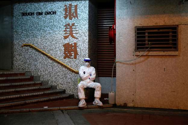 Slide 1 of 116: A man in protective gear waits to evacuate residents from a public housing building following the outbreak of the novel coronavirus, in Hong Kong, China February 11, 2020. REUTERS/Tyrone Siu REUTERS/Tyrone Siu