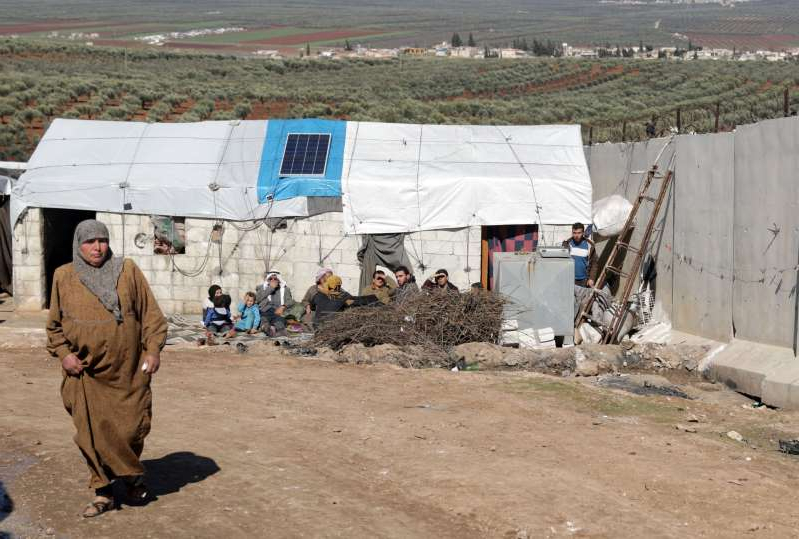 a man that is standing in the dirt: FILE PHOTO: Internally displaced Syrian woman walks near the wall in Atmah IDP camp, located near the border with Turkey
