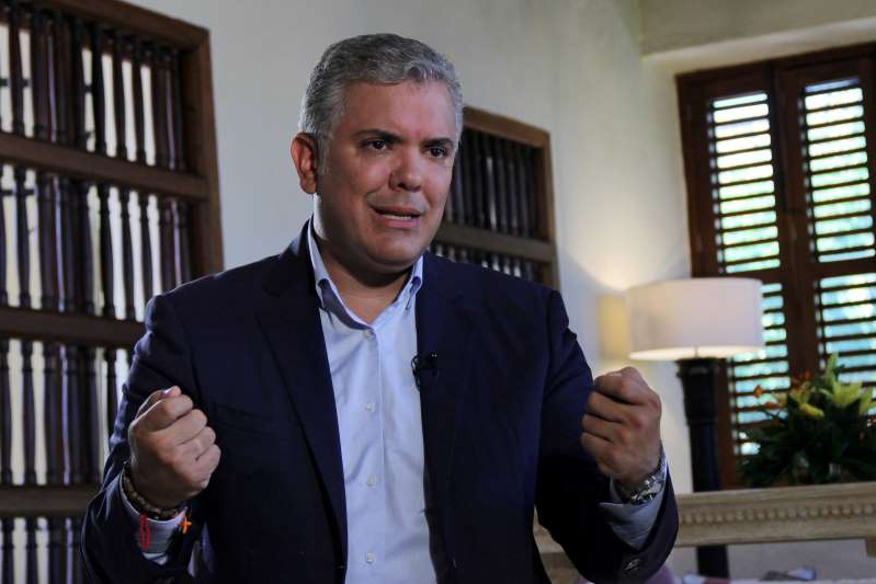 a man wearing a suit and tie: FILE PHOTO: Colombia's President Ivan Duque speaks during an interview with Reuters in Cartagena