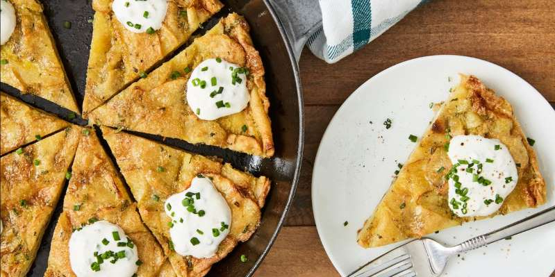 a plate of food on a table: A traditional Spanish dish, a Spanish tortilla is basically a gussied up omelette. In our recipe, we throw in some potato chips for texture, add some garlic for flavor, and top the whole shebang with a creamy, dreamy sauce.