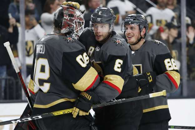 Vegas Golden Knights defenseman Nate Schmidt, left, defenseman Brayden McNabb (3) and Robin Lehner (90) celebrate after defeating the Buffalo Sabres in an NHL hockey game Friday, Feb. 28, 2020, in Las Vegas. (AP Photo/John Locher)