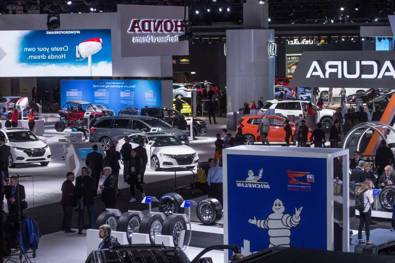 a crowd of people in a car: A view of the show floor during the 2019 North American International Auto Show held at Cobo Center in downtown Detroit on Monday, Jan. 14, 2019.