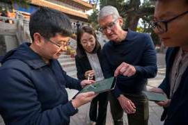 Tim Cook et al. looking at a cell phone