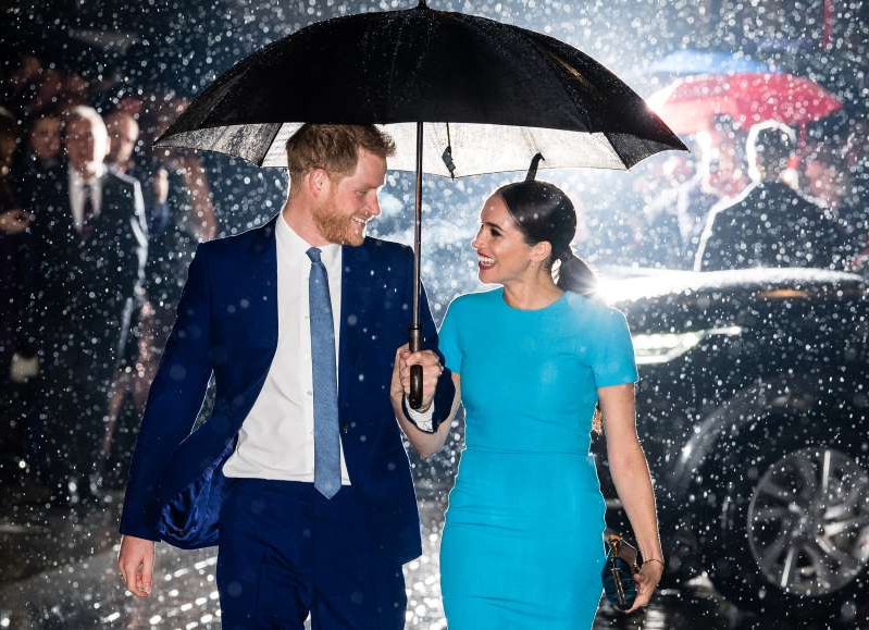 a man that is standing in the rain holding an umbrella: LONDON, ENGLAND - MARCH 05: Prince Harry, Duke of Sussex and Meghan, Duchess of Sussex attend The Endeavour Fund Awards at Mansion House on March 05, 2020 in London, England. (Photo by Samir Hussein/WireImage)