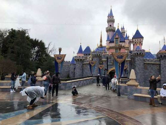 Slide 1 of 47: Visitors take photos at Disneyland in Anaheim, Calif., Friday, March 13, 2020. Disneyland is closing its doors for the rest of the month, shuttering one of California's best-known attractions as the state hurries to stop the spread of the coronavirus. (AP Photo/Amy Taxin)