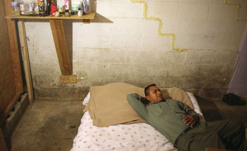 a person lying on a bed: Toribio Jimenez lays on his bed in his bedroom of the home where he and 10 other people live. His bedroom is in the basement of the house. Jimenez was given a job in the U.S. through the H2B visa program but when he arrived in the U.S., the job he was given paid much less that he was originally offered. He now has little money to find a better place to live and does not have enough money to go back to South America. (AP Photo/Josh Anderson)
