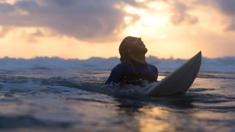 a person riding a surf board in the water: Rise and Shine: What you need to know before the ASX opens