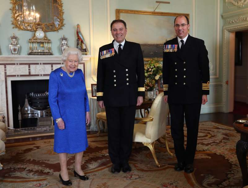 a person standing in front of Elizabeth II et al. posing for the camera: Queen Elizabeth II receives Commodore Steven Moorhouse (centre, outgoing Commanding Officer, HMS Queen Elizabeth) and Captain Angus Essenhigh (incoming Commanding Officer), during a private audience in the Queen's Private Audience Room, at Buckingham Palace, London. PA Photo. Picture date: Wednesday March 18, 2019. Photo credit should read: Yui Mok/PA Wire