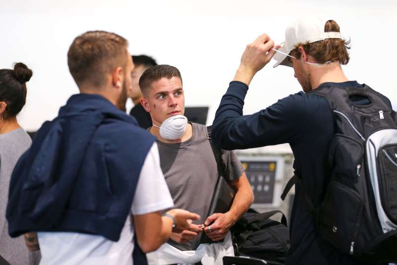 WELLINGTON, NEW ZEALAND - MARCH 18:  Cameron Devlin looks on as Alex Rufer tries on his face mask at Wellington Airport, prior to the departure of the Wellington Phoenix team to Sydney to complete the remainder of the Hyundai A-League season on March 18, 2020 in Wellington, New Zealand. (Photo by Hagen Hopkins/Getty Images)
