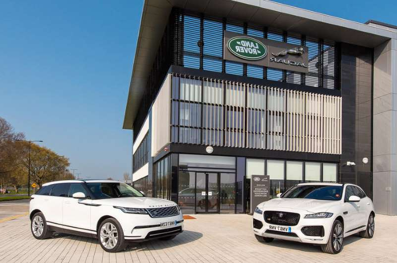 a car parked on the side of a building: Jaguar Land Rover and Bentley halt production for a month