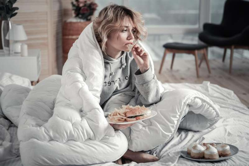 a woman sitting on a bed: Junk food during social distancing